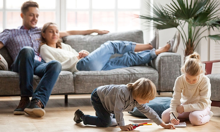 Couple with relaxing on couch watching children playing